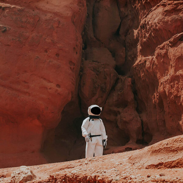 Man in spacesuit stands in desert.